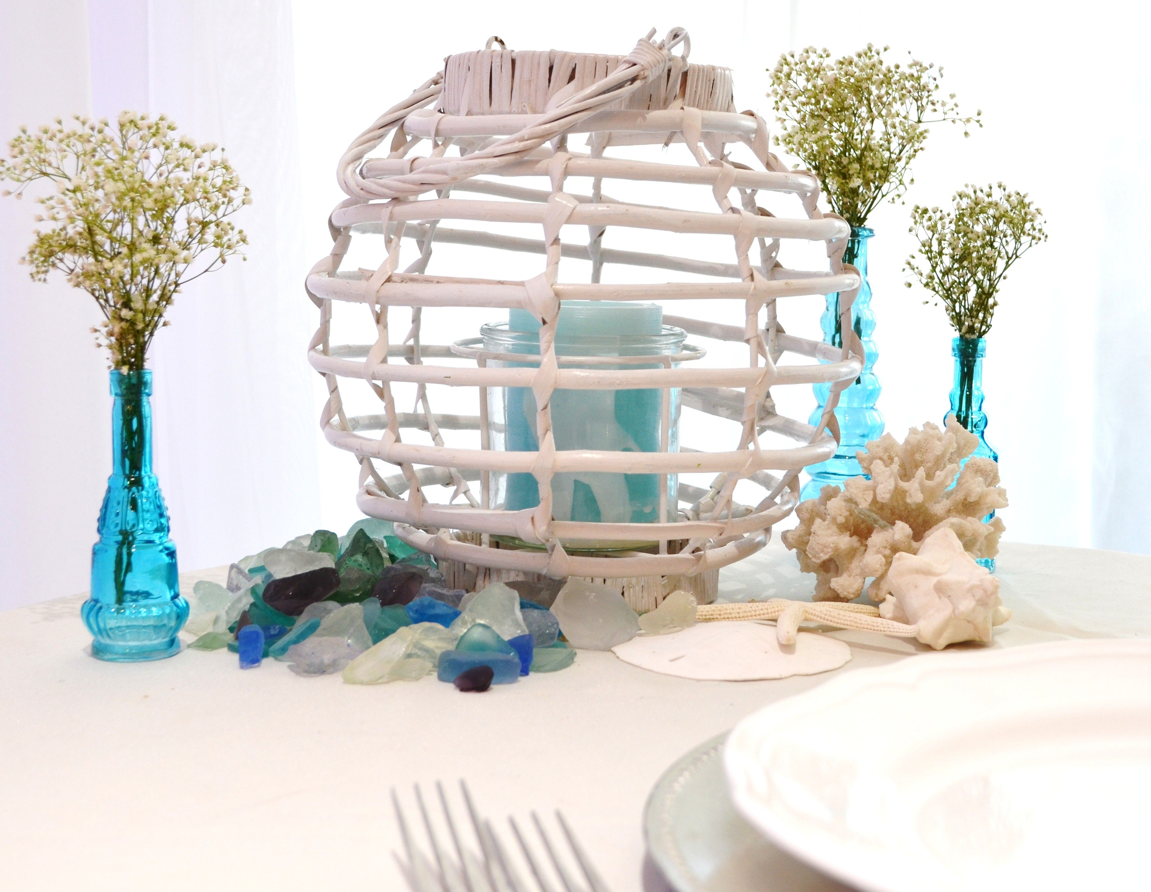 white wicker lantern, turquoise bud vases, white sea life, sea glass ...