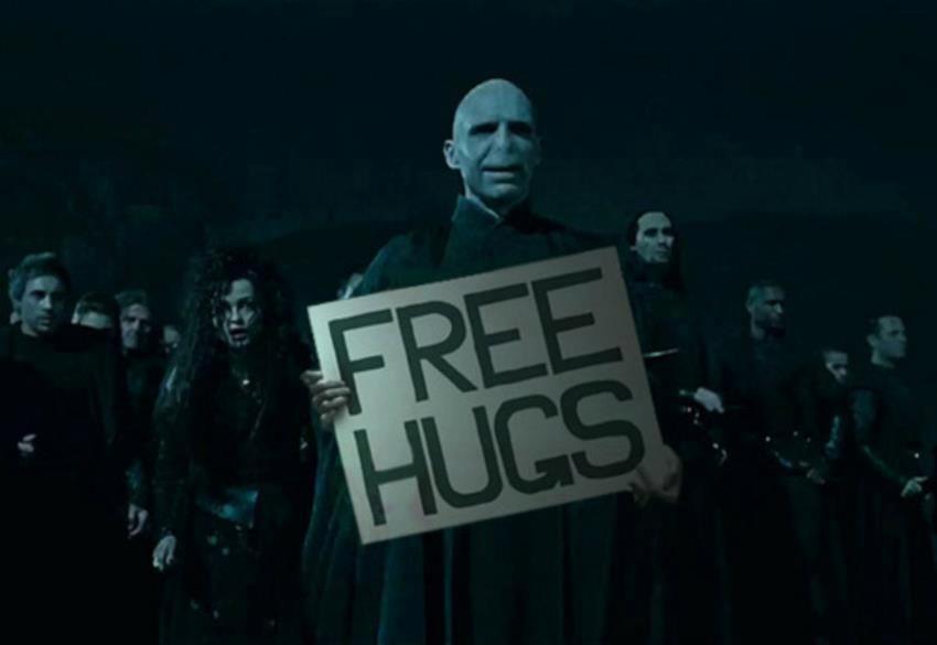 """Za temné noci je Voldemort v popředí svých Smrtijedů (vlevo za ním je Bellatrix). Voldemort drží velkou ceduli s nápisem """"Free Hugs""""."""