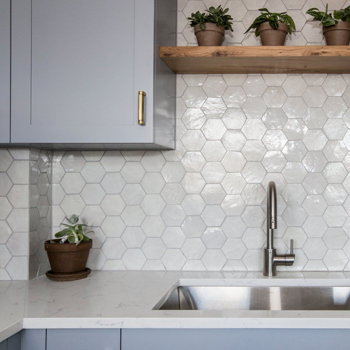 details. fun installation of our glazed terracotta zellige in weathered white hexagon tiles in this kitchen backsplash. notice the continuation through the corner. need assistance with trim? just ask clé. #backsplash #zellige #kitchen #tile