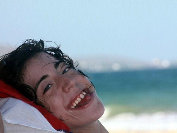 Joven sonriente, con el mar al fondo