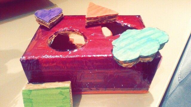 Caja sensorial, para que los niños asocien las diferentes formas y las introduzcan dentro de la caja. Se trabaja la vista y la asociación de formas.  Materiales: caja de cartón, celofán de colores, rotuladores,cúter, tijeras.
