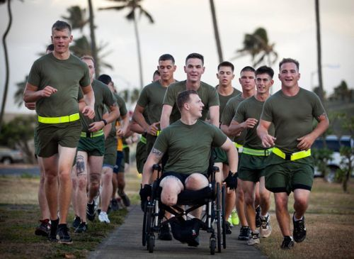 Cpl. Garrett Carnes (in wheelchair), a squad leader with 3rd Platoon, India Company, 3rd Battalion, 3rd Marine Regiment, and 22-year-old native of Mooresville, N.C., jokes with Sgt. Kenney Clark (right), a fellow India Co. squad leader, during a motivational run held here, May 29, 2012, to honor Carnes' life and sacrifice. The infantryman lost his legs in an improvised explosive device attack Feb. 19 while supporting combat operations in the Khan Neshin district of Afghanistan's Helmand…