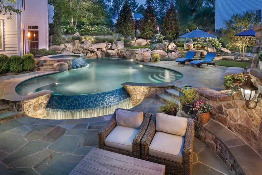 A Freeform Pool And Raised Spa Boast Spillways Clad In Mosaic Tile Set Into Grade With A