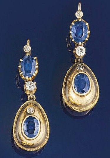 A pair of sapphire and diamond earpendants  Each egg shaped drop with single oval sapphire collet and diamond accent to an old-cut diamond single stone suspension and oval sapphire and diamond two stone surmount, hook fitting