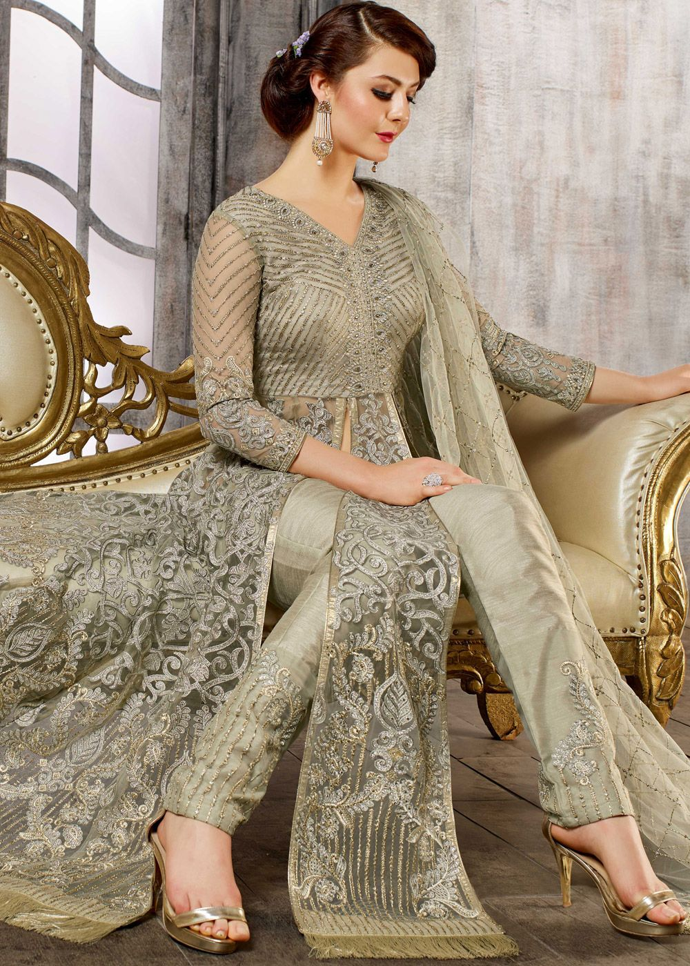 28ad803c05 Featuring a ravishing moss green net front slit kameez adorned with zari,  resham embroidery, lace, stone work and tassels at hemline.