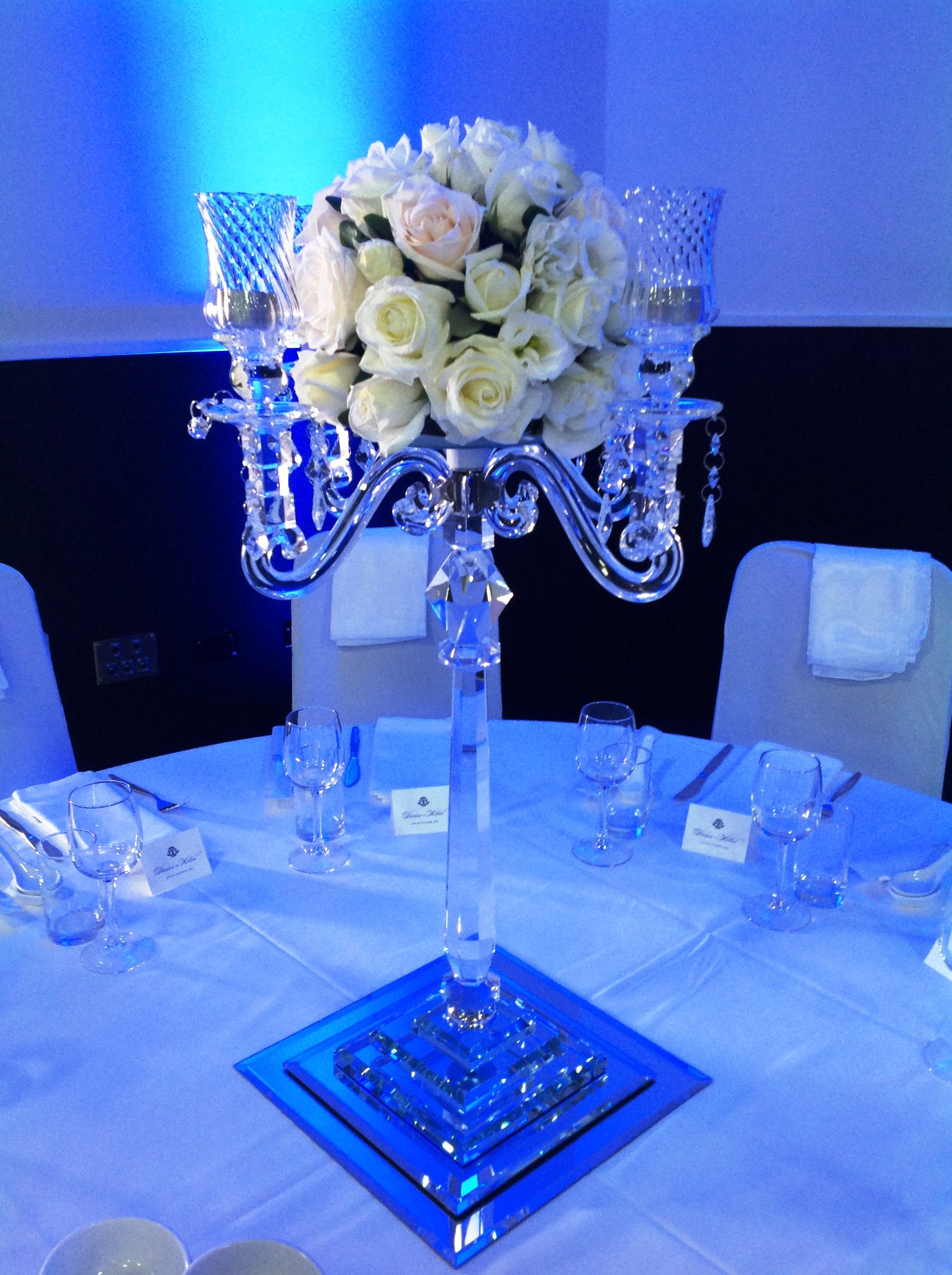 Rose arrangement on top of 4 arm crystal candelabra with square mirror base. www.houseofthebride.com.au