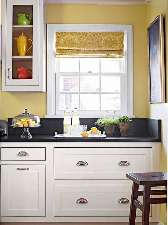 Dark Stone Countertops And A Coat Of Clean White Paint Allows This Kitchen S Charming Craftsman Inspired Cabinetry To Pop Against Warm Yellow