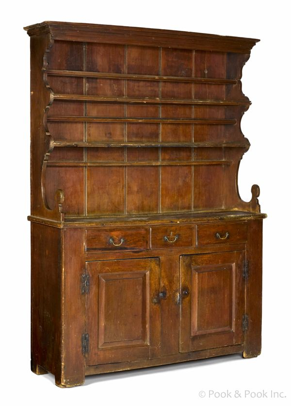 "Pook & Pook. April 25th 2014. Lot 90. Pennsylvania stained pine and poplar pewter cupboard, ca. 1770, the open top with original scalloped sides & lollipop terminals, above 3 drawers & 2 raised panel doors supported by bracket feet, retaining an old red surface, 83 1/2"" h., 60"" w. Estimated: $10K - $20K.  Condition:   Original brasses. Several drawer lip repairs. Repair to cornice molding. Hinges replaced."