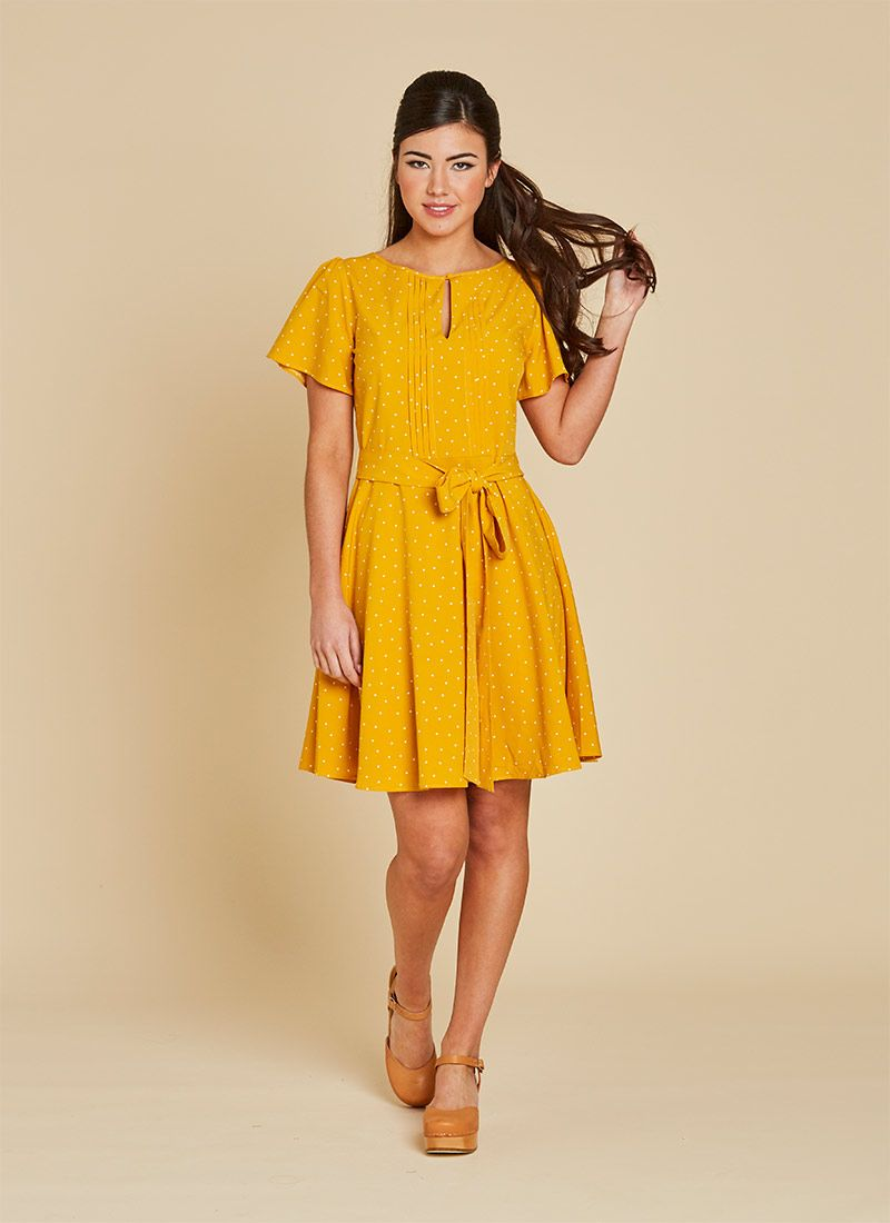 ff592fb5f30 Celia is a classic tea dress in a yellow and white mini polka dot with a