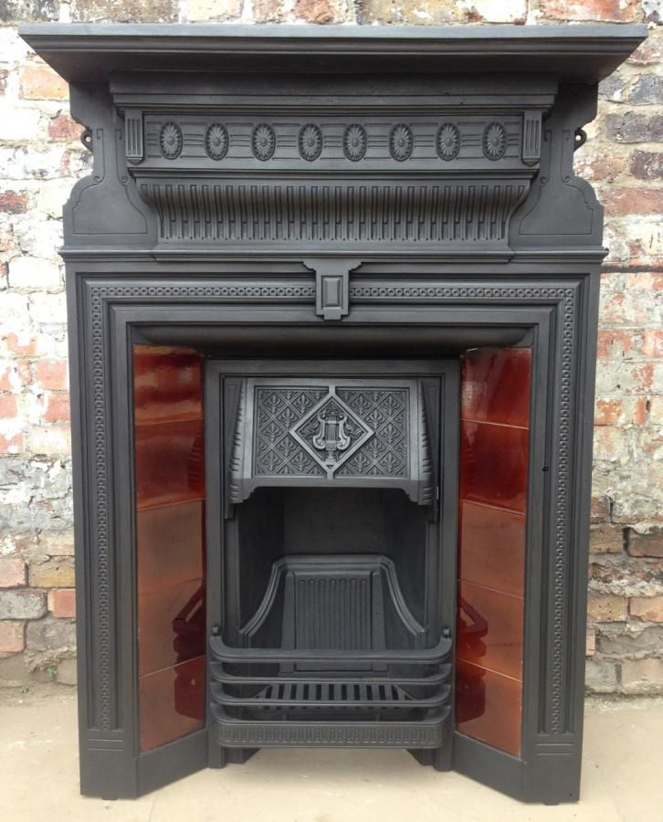 An original Edwardian antique cast iron fireplace with tiles for