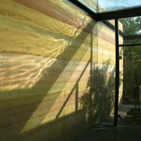 Light Passing Through Water On The Glass Roof Is Animating This Rammed Earth Wall Rammed Earth Earth Roof Rammed Earth Homes