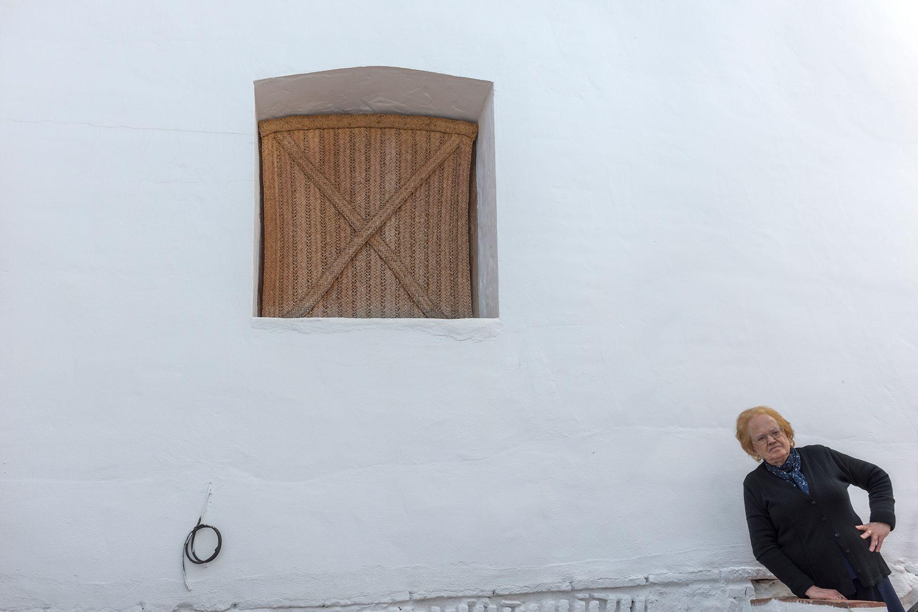 Mujer curiosa y ventana con cortina de esparto