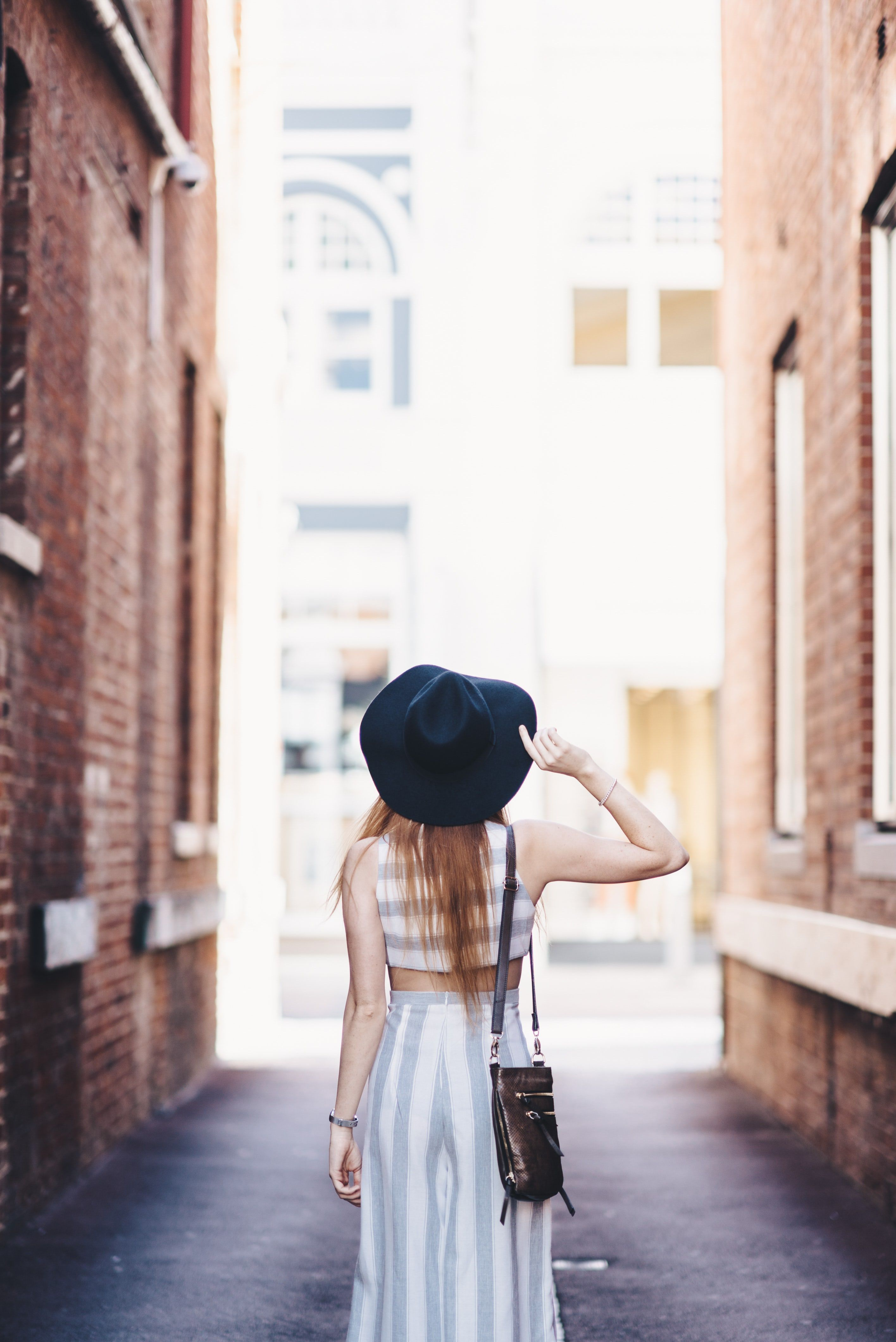 A woman in a hat walks away from the camera in an alleyway