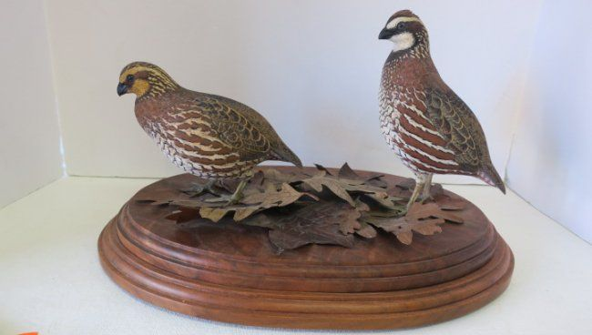 """Bob White Quail Wood Carving: Fully Detailed Life Size Carving Standing on Bed of Metal Oak Leaves on Multilever Beveled Oval Base. Handpainted with Glass Eyes. Male and Female with Exceptional Detail and Awareness. 16"""" X 11"""" X 9""""T. (2000-4000)"""