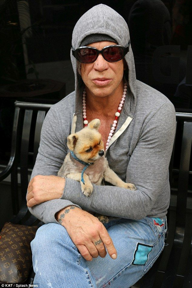 Mickey Rourke cuddles one of his pups as he sits on a