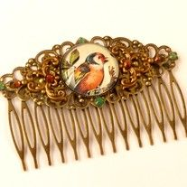 This wide hair comb is made of bronze metal. On the flourishes ornament I have a metal frame with hand-made glass cabochon, which shows a beautiful bird motif attached. To both sides are brass ornaments. The hair comb is also decorated with Swarovski rhinestones in green and brown.   The comb h...