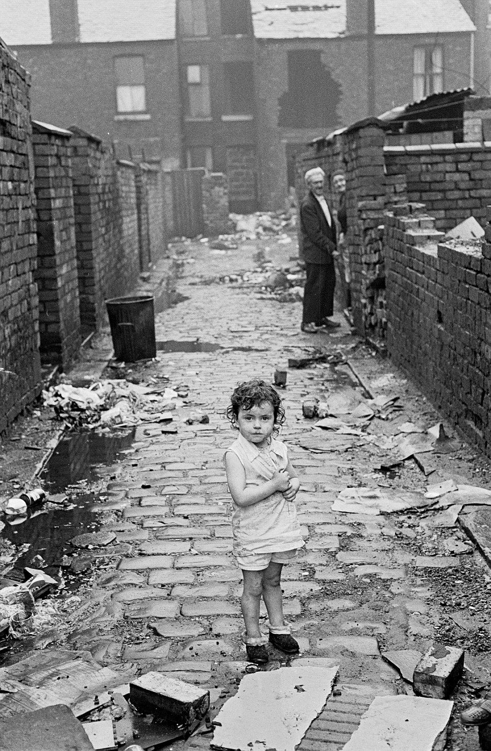 This child stares at the camera in the Manchester street, wearing barely any clothes, as an older couple watch in the background