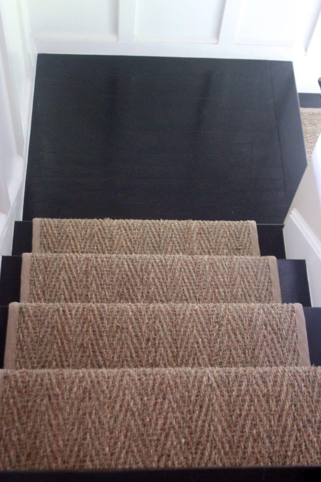 White walls. Black floor. Natural rug.