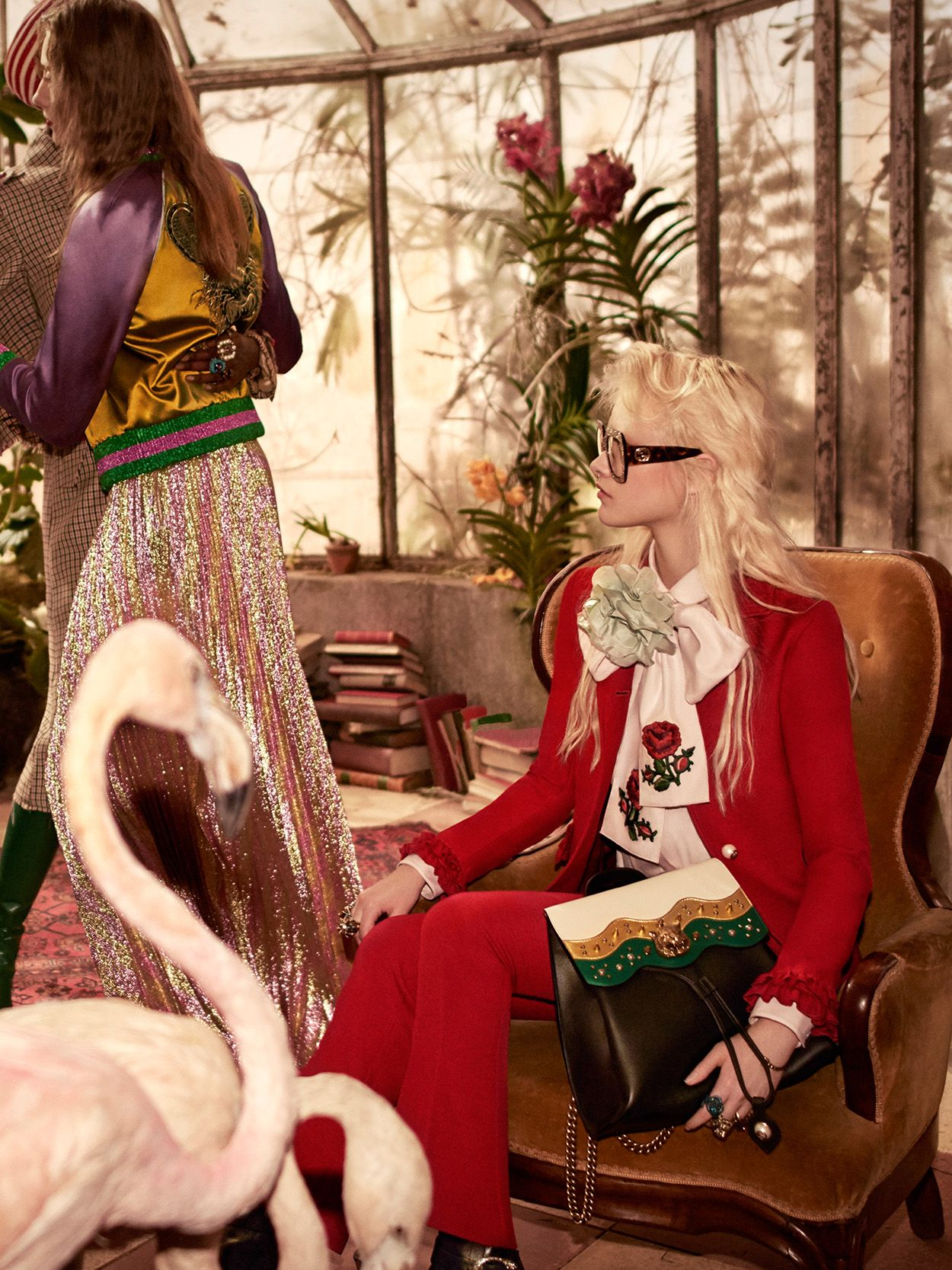 Floral and feline embellishments in the women's Gucci Pre-Fall 2016 collection: a flower neck tie accents a hibiscus red crêpe suit and golden studs and a feline head decorate a multicolored leather backpack.