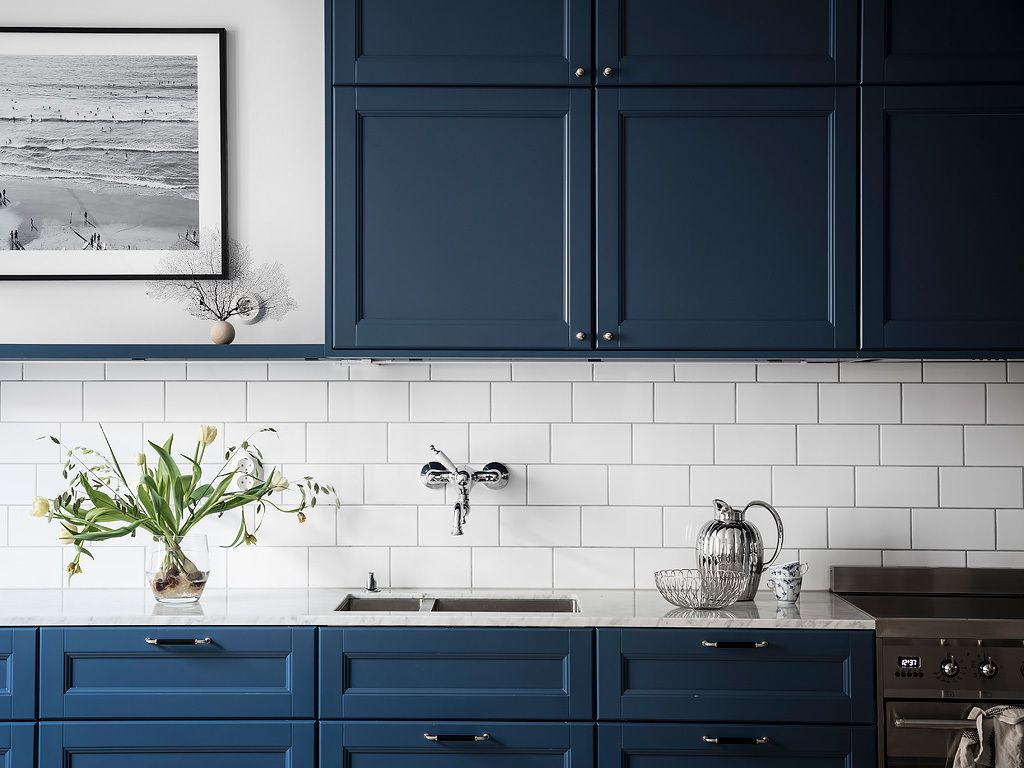 High-contrast slate-blue cabinets with white subway tile backsplash ...