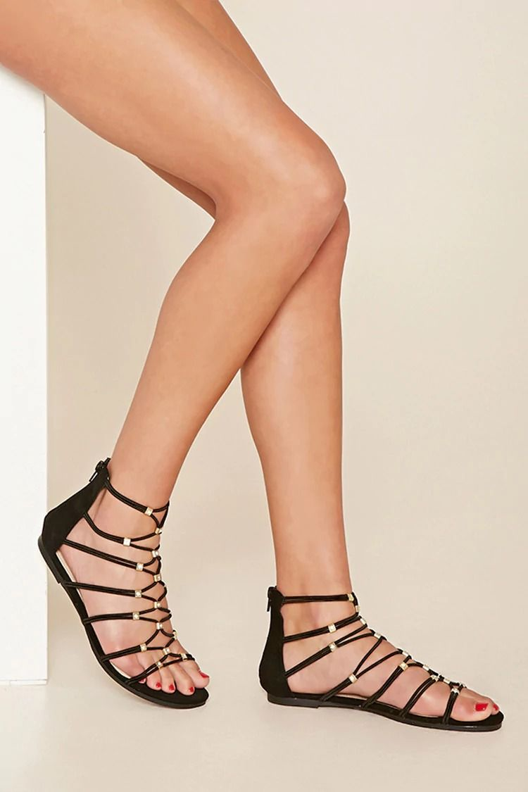 0873f2ccf2d506 A pair of faux leather gladiator sandals with a banded strappy design and a  back zipper closure.
