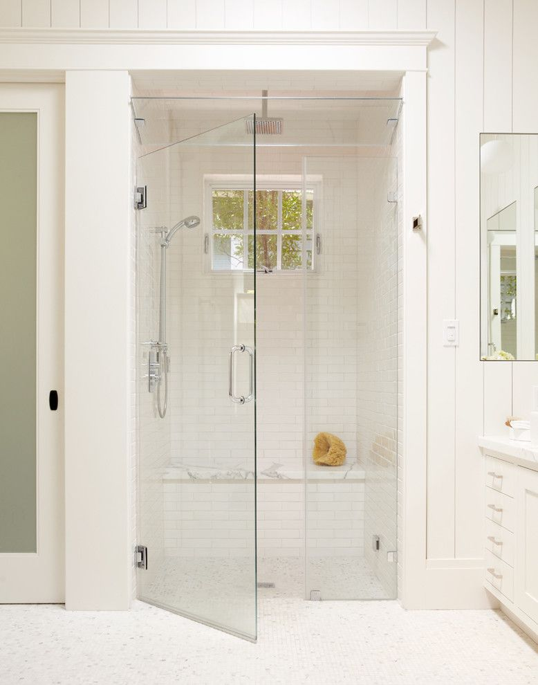 Large white tile shower with bench, steam shower, and window for ...