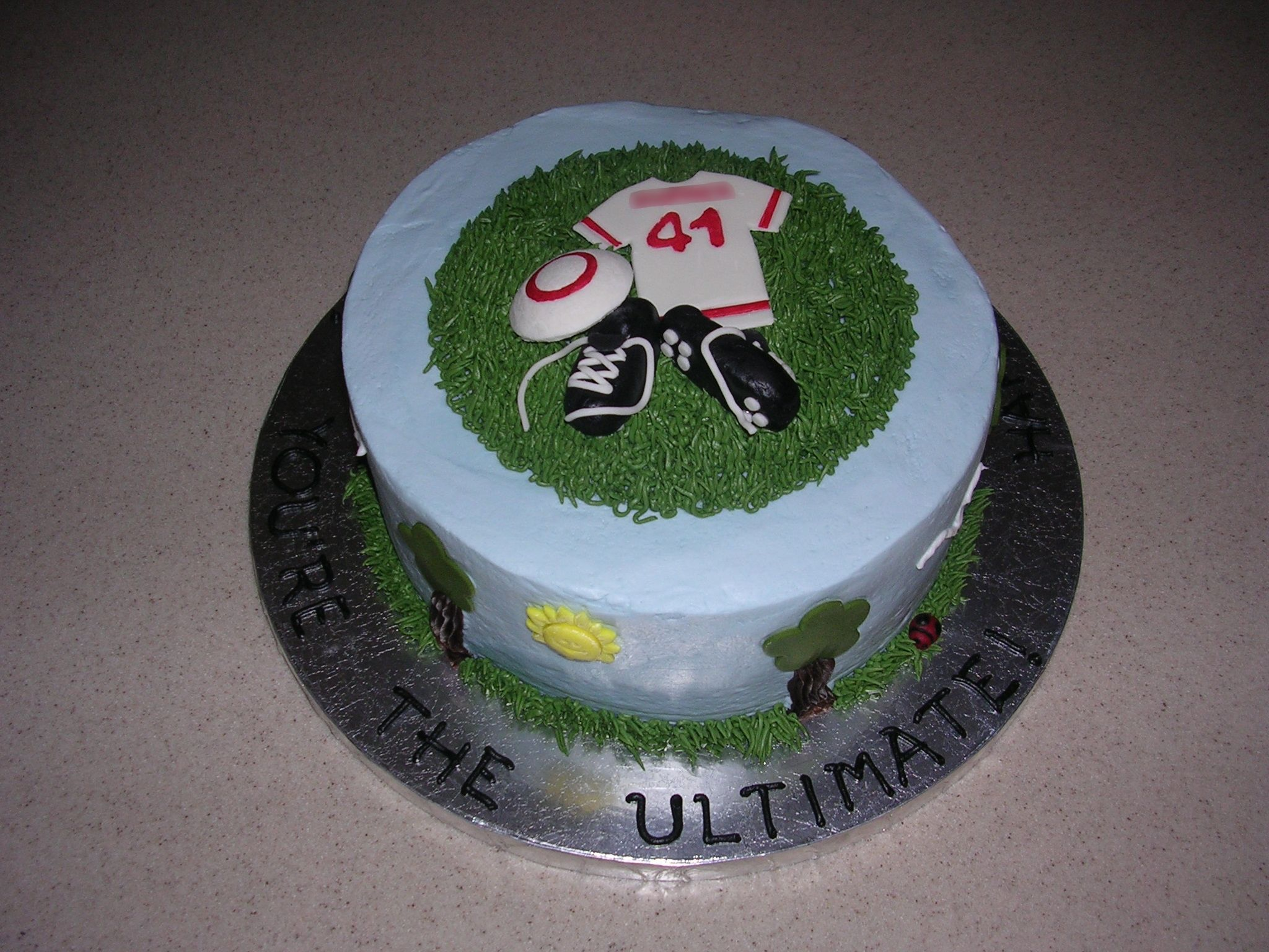 """Ultimate Frisbee - I made this cake for my husband's 41st birthday. He plays the sport of Ultimate, similar to frisbee football. It's an 8 inch chocolate cake with chocolate filling and iced with buttercream.  Grass, tree trunks and birds are buttercream.  Sun, tree tops, ladybugs, shoes, jersey and disc (frisbee) are either fondant or fondant/gumpaste. Last name obscured for privacy.  Words on the cake board read """"Happy Birthday Daniel, You're the Ultimate!"""""""