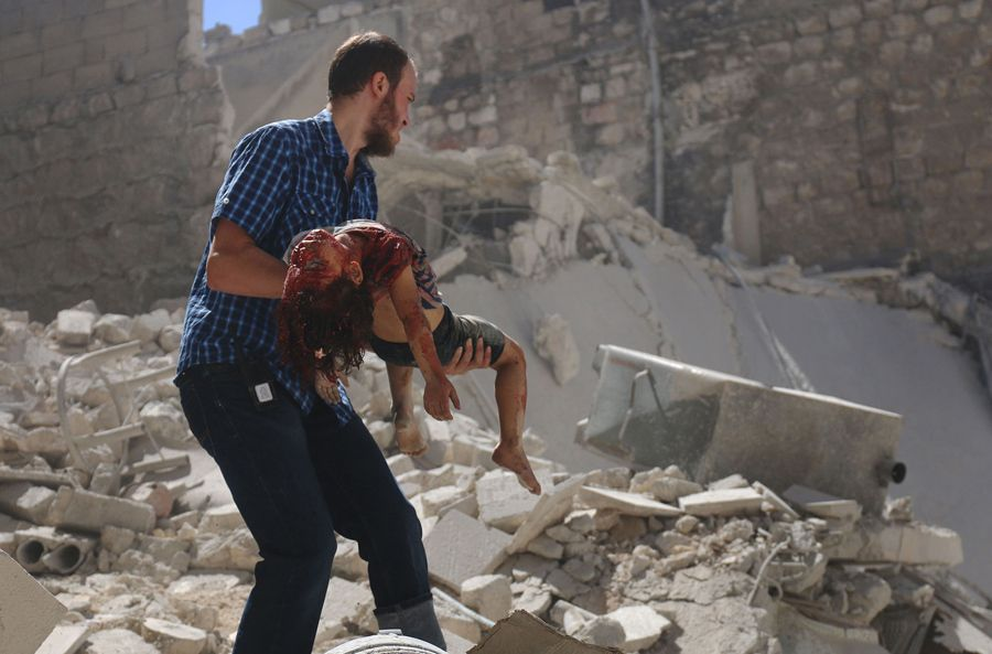 A Syrian man carries the body of a girl after she was trapped under the rubble following reported air strikes on the rebel-held neighbourhood of al-Mashhad in the northern city of Aleppo, on July 25, 2016.