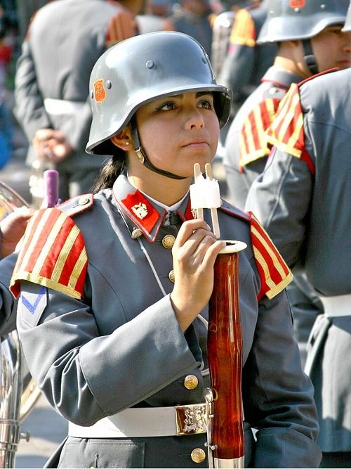 A Chilean military band member eating a popsicle while ...