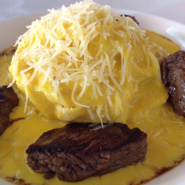 Spaguetti Huancaina, salsa a base de ají amarillo, quesos y crema de leche, bañando la pasta y acompaña lomos finos a la plancha. El Grifo.