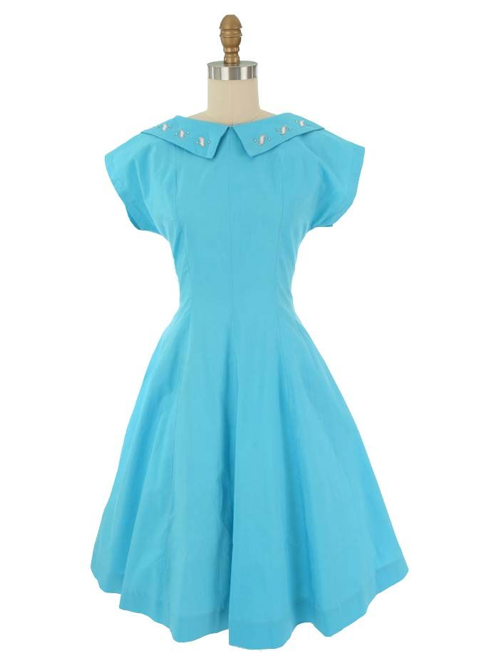 Authentic swing dress from the 50s in turquoise cotton with figure flattering princess seaming. Rhinestones and studs on collar add a nice touch of bling.