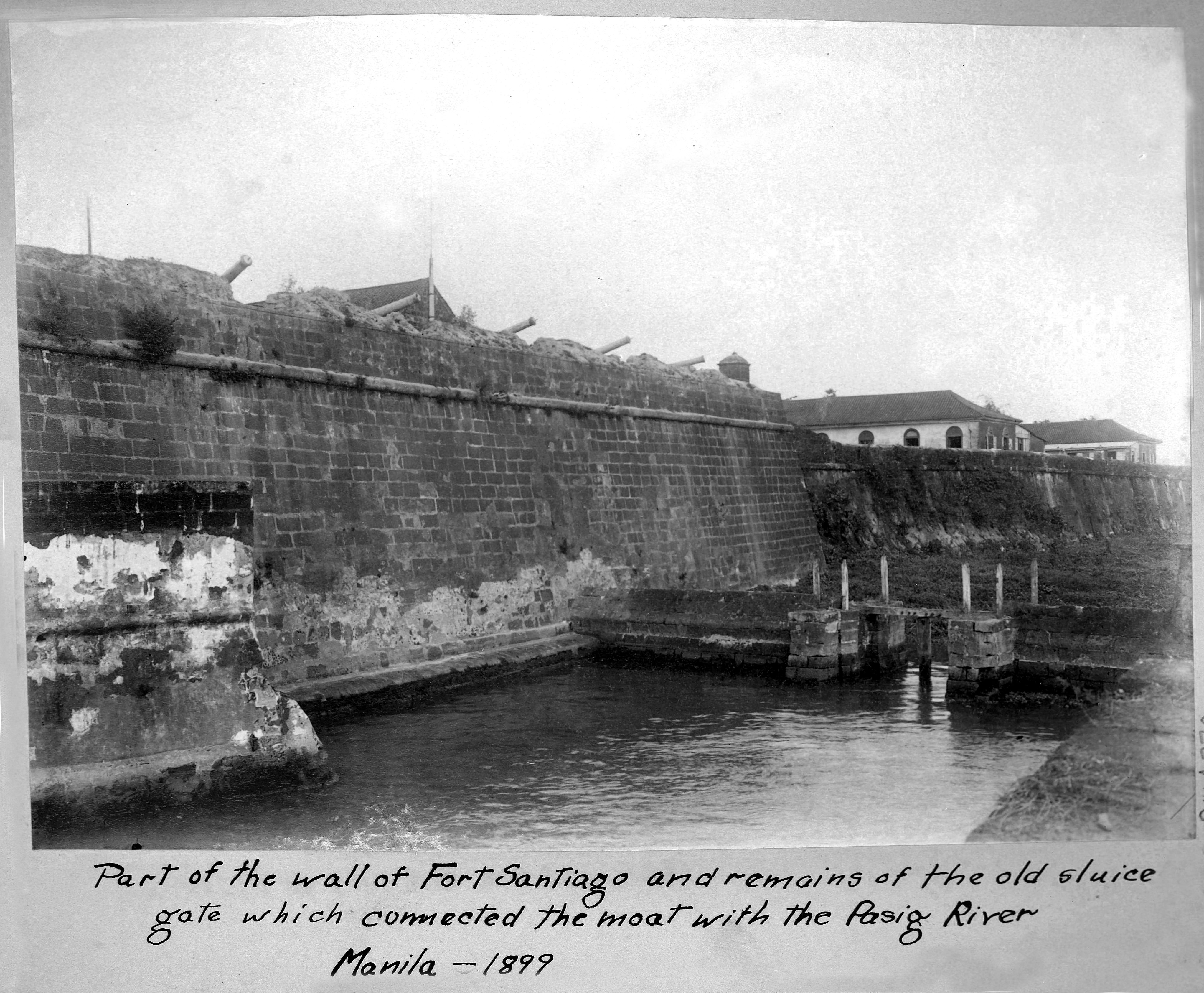 Photograph of a portion of the wall at Fort Santiago and remains of the old sluice gate which connected the moat with the Pasig River. Photo taken in Manila in 1899. The moat was later deemed a health hazard and breeding ground for mosquitos. It was later filled in and is now a gold course.