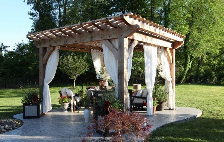 schöne Pergola aus Massivholz mit schönen Gartenmöbeln und weißen ...