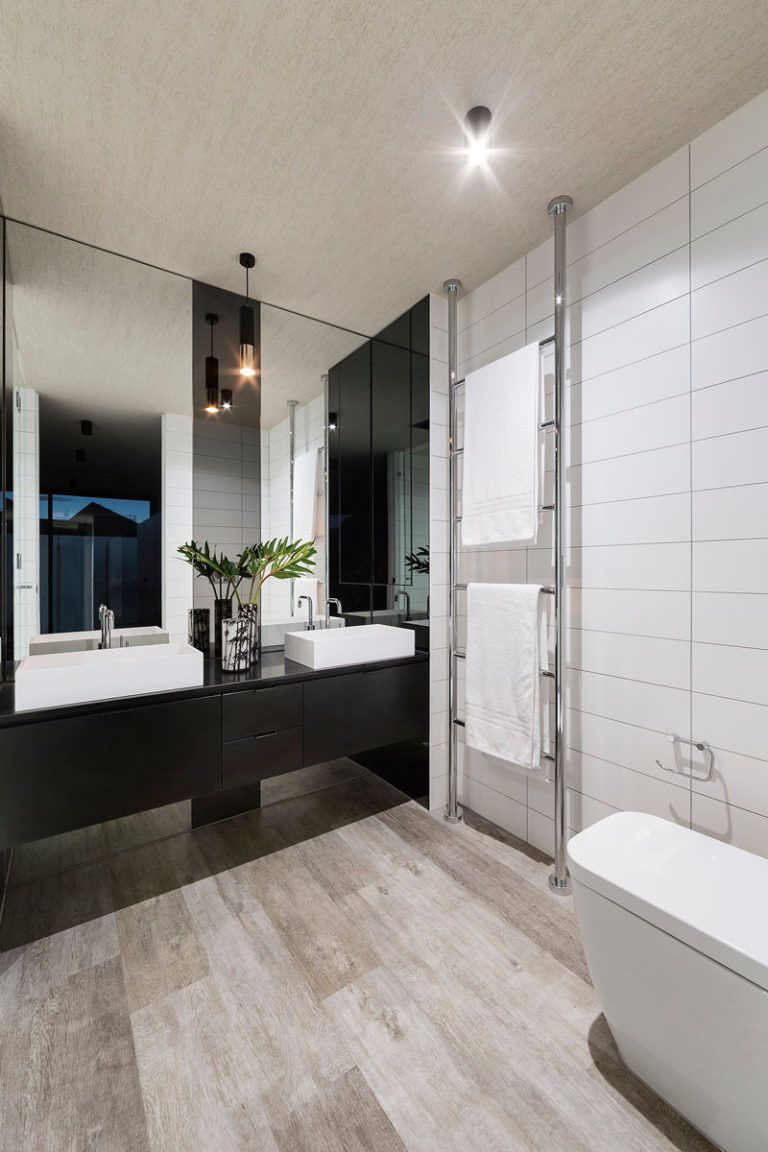 This Bathroom Has Dual Sinks Large White Tiles And A Towel Rack