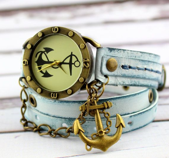 Lightly distressed blue womens leather wrap watch with antique brass anchor watch face. The band features brass color studs, matching chains and an anchor charm complete the design. The wrap watch is made with veg tanned leather, completely handmade. The strap length is 30 inches and it will go around your wrist 3-4 times! It will fit for all wrist sizes. Watch face size: 1 1/2 wide If you would like to purchase any of the straps you see here or if you would like me to build a custom st...