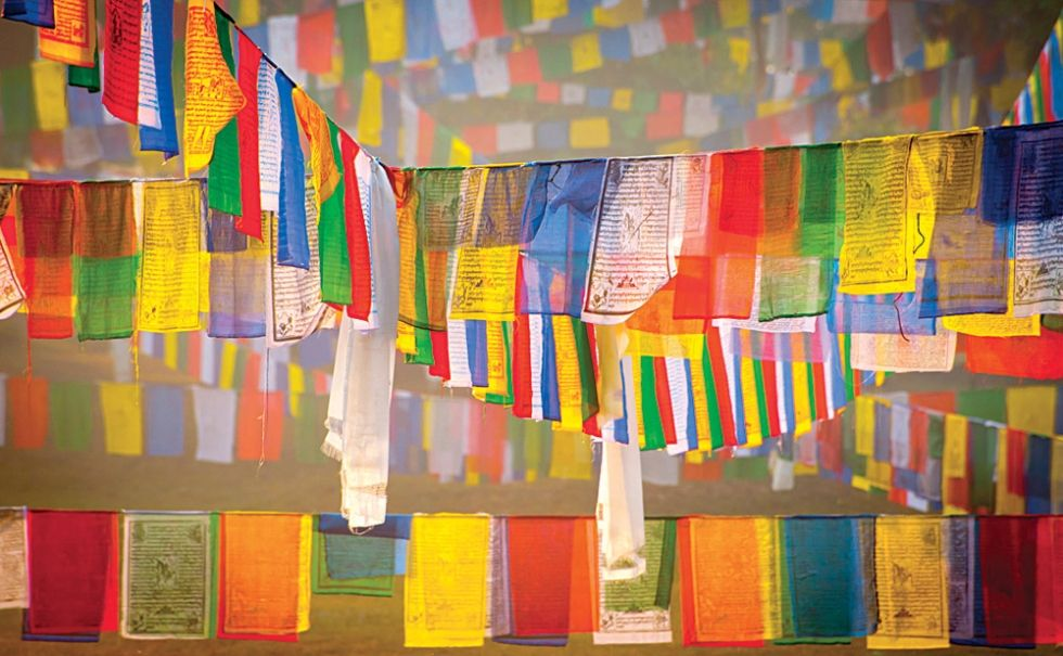 Prayer flags at the Bodhi Tree in Lumbini, Nepal.  Photo by Christian…