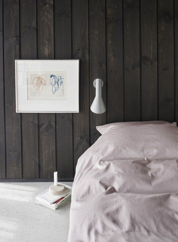 Dark wooden panelling in the bedroom and soft pink bedding create a beautiful contrast