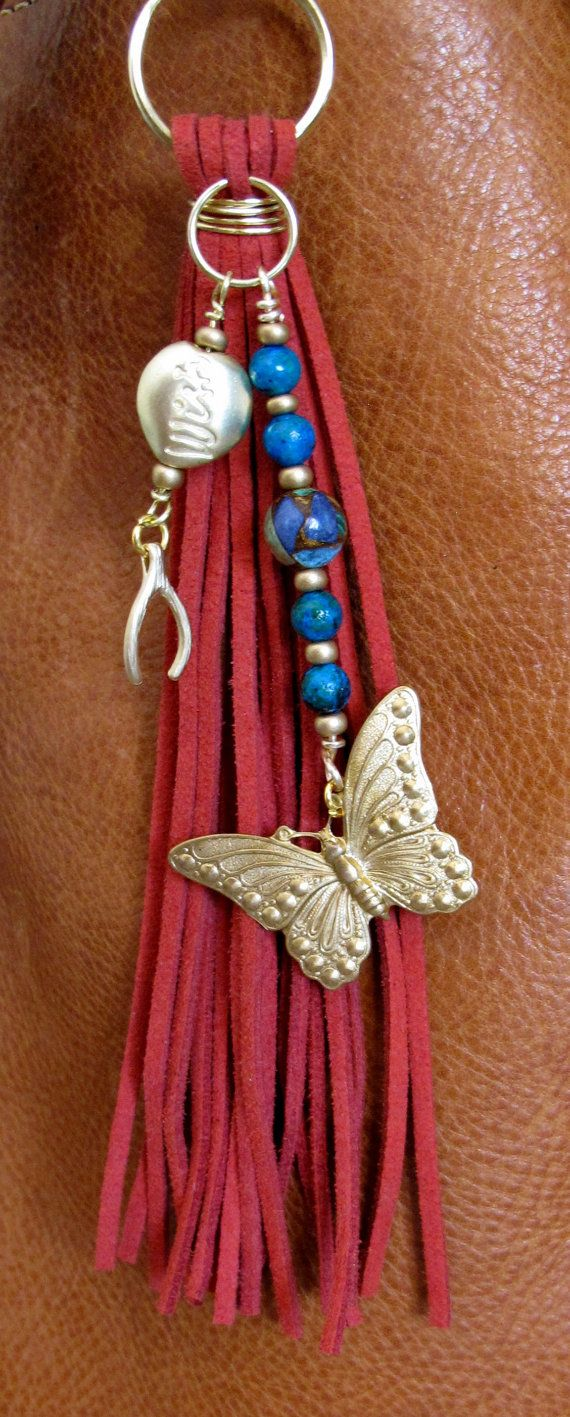 #ThePaintedCabeza ~ This handmade tassel charm can be used on your purse, backpack, zipper, wherever youd like to add some charm! Its made up of red suede, turquoise colored stone beads, glass beads, a beautiful lapis malachite bead, and brass charms - a beautifully detailed butterfly and a wishbone, and a golden glass stone with wish written on it. Altogether, the charm is approximately 7.75 long.