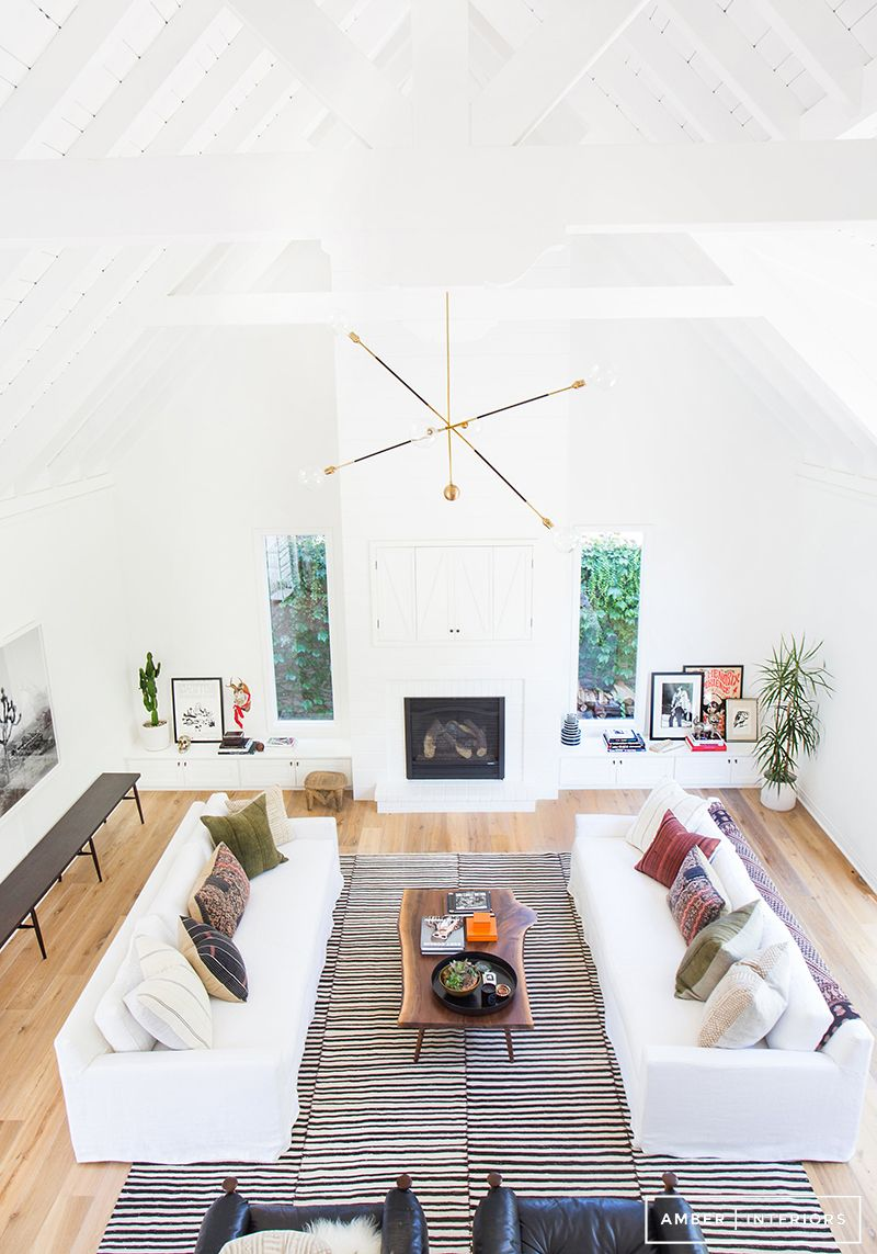 Open living room with white couches, brass chandelier, and geometric ...
