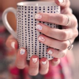 Created with red, white, and blue nail polish for the 4th of July, this dotted manicure would be cute in any colors!