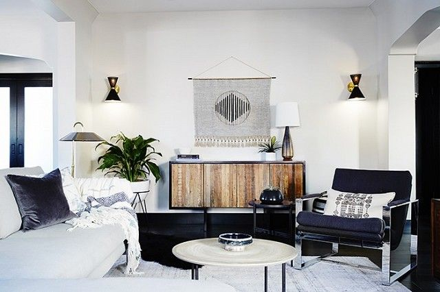 Living space with a gray sectional, a dark gray armchair, and black sconces