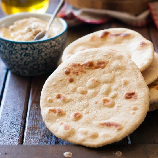 The dough for the pitas is made from a combination of spelt and einkorn flours. These pitas are flat with some bubbles.
