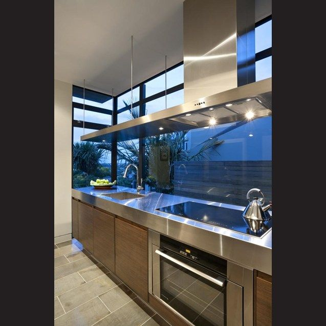 The oven and hood are set off centre to leave room for the sink. Extending the hood over the length of the 3.6m perimeter island brings aesthetic balance to this area of the kitchen.