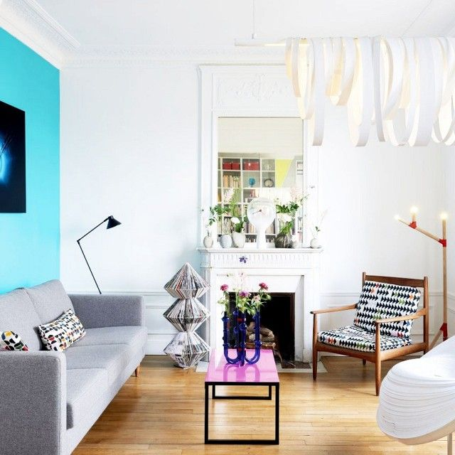 Bright living space with a gray sofa, a bright blue statement wall, and a modern coffee table