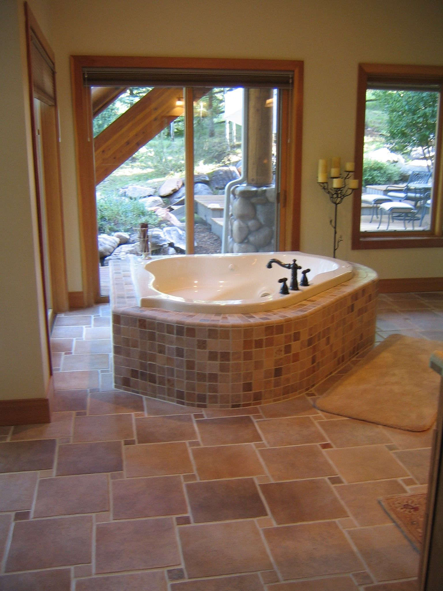 Freestanding triangular tub surrounded by sliding glass windows and ...