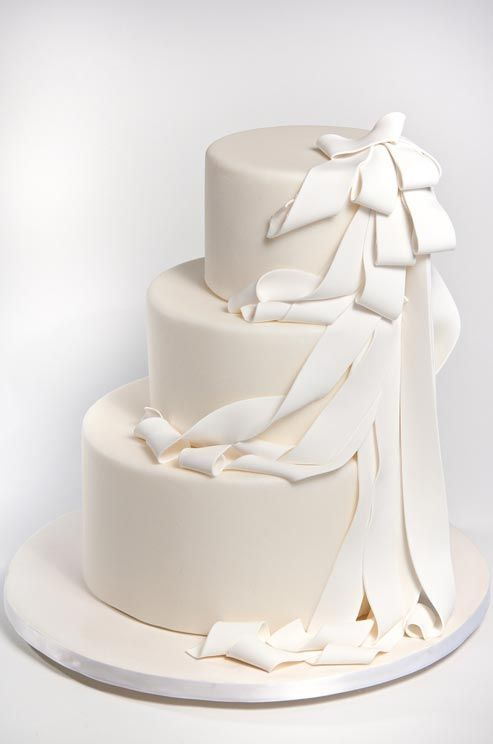 This off-center cream wedding cake is draped in flowing white fondant ribbons.