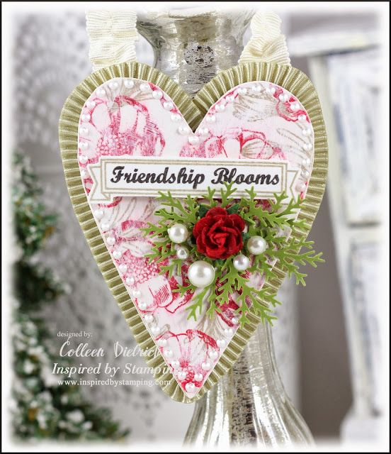 Heart shaped wooden ornament, decorated with hand-stamped flowers from Inspired By Stamping.  Pleated ribbon, sentiment banner, branch punched greens, pearls and a red rose top it off.