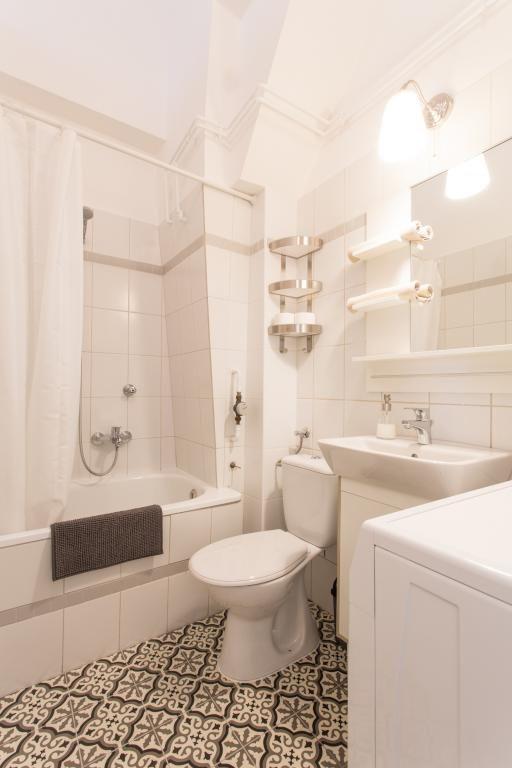 Schönes Badezimmer mit gemustertem Fliesenboden und weißen ...