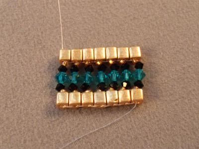 The first row completed.  Note the thread coming out of the top of the last set of beads.