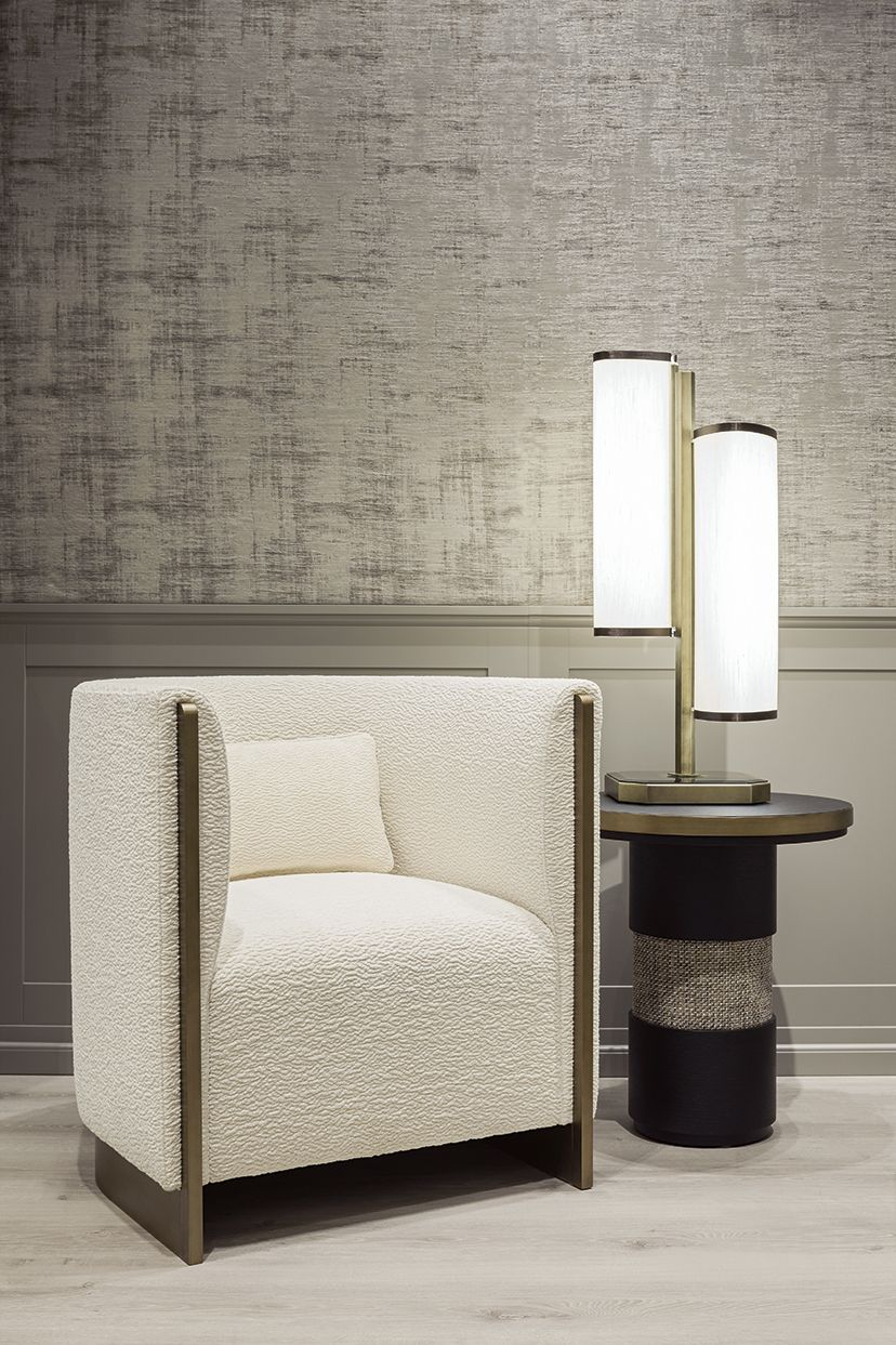 """At the 2017 Salone del Mobile in Milan, Oasis presented a captivating and unprecedented """"total look"""" environment.  A sitting area is made up of two beautifully contoured Adeline armchairs with bronze frame together with round Eros side tables featuring a fabric and black oak base. Flower table lamp."""
